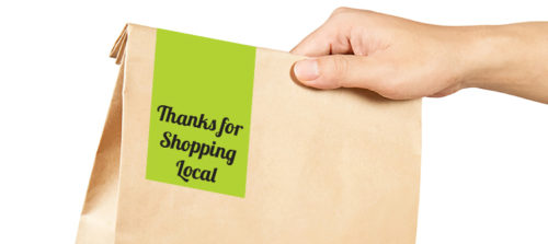 Right hand holding a brown paper bag with green label sealing bag
