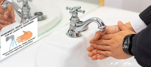 Businessman washing hands in sink with window decal about washing hands