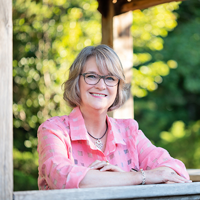 Patti Fairchild, Sales associate with arms leaning on wooden gazebo